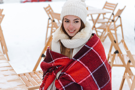 Photo pour Image of a pretty young woman in hat and scarf walking outdoors in winter snow wearing plaid. - image libre de droit