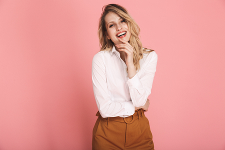 Portrait of cheerful blond woman 30s in stylish outfit smiling and looking at camera isolated over red background