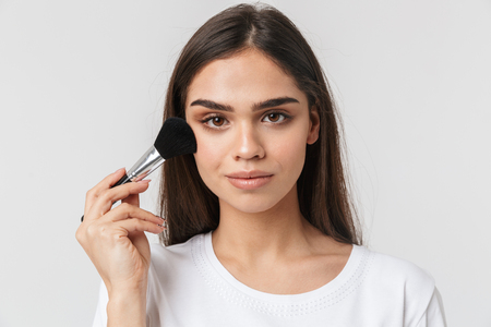 Close up portrait of a pretty young woman casualy dressed isolated over white, applying makeup with a brush