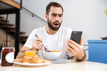 Foto de Handsome shocked young man having breakfast while sitting at the kitchen, holding mobile phone - Imagen libre de derechos