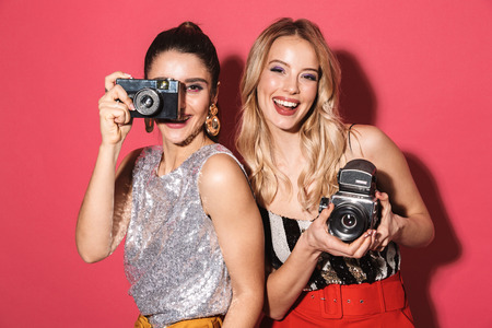 Foto de Image of two adorable girls 20s in stylish outfit holding and photographing on retro camera isolated over red background - Imagen libre de derechos