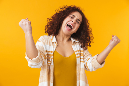 Photo pour Image of happy woman 20s with curly hair screaming and rejoicing, isolated over yellow background - image libre de droit