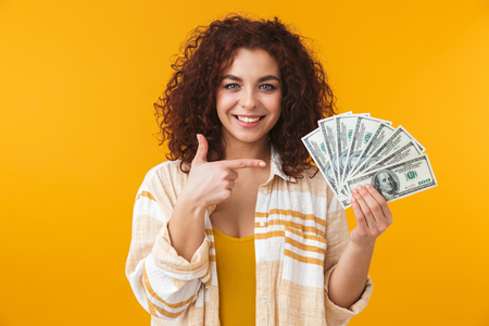 Photo pour Image of a cute beautiful emotional young curly girl posing isolated over yellow wall background holding money. - image libre de droit