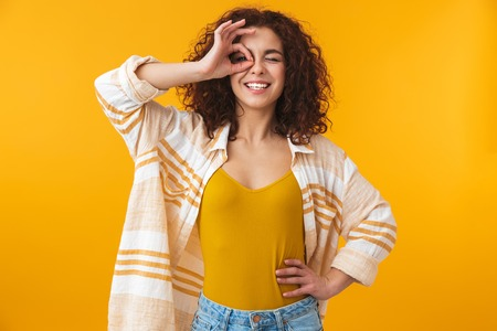 Foto de Image of a beautiful young curly girl posing isolated over yellow wall background with okay gesture. - Imagen libre de derechos