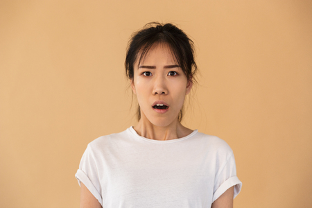 Photo for Portrait of confused asian woman wearing basic t-shirt wondering and looking at camera with open mouth isolated over beige background in studio - Royalty Free Image