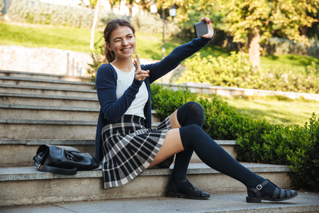 Photo for Cheerful young school girl sitting outdoors on staircase, using mobile phone, taking selfie - Royalty Free Image