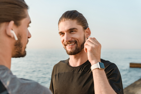 Photo for Two twin brothers doing exercises at the beach together, talking - Royalty Free Image