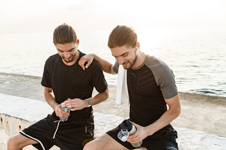Photo for Two twin brothers doing exercises at the beach together - Royalty Free Image