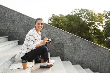 Cheerful young teenage girl sitting on a staircase outdoors, making picture with photo camera