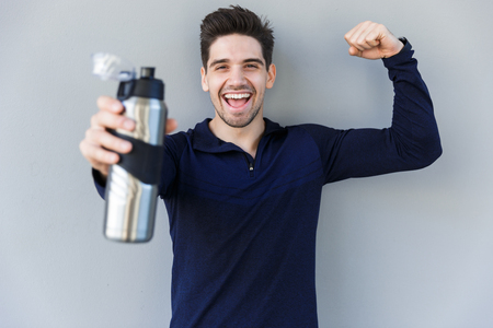 Foto de Confident smiling sportsman holding water bottle while standing isolated over gray background - Imagen libre de derechos