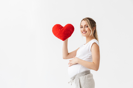 Foto de Beautiful young pregnant woman standing isolated over white background, holding heart - Imagen libre de derechos