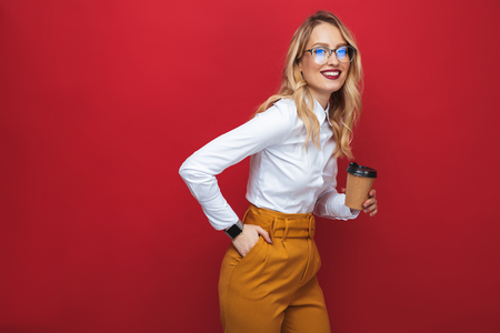 Foto de Smiling beautiful young blonde woman standing isolated over red background, holding takeaway coffee cup - Imagen libre de derechos