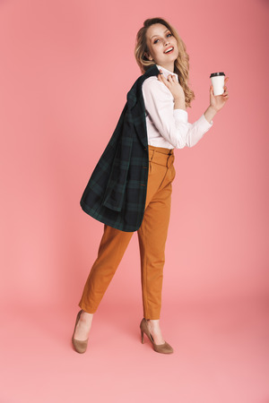 Photo for Image of beautiful woman 30s in trendy jacket walking and drinking takeaway coffee isolated over pink background - Royalty Free Image