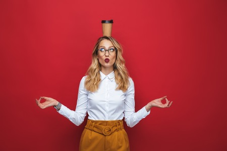 Foto de Beautiful funny young blonde woman standing isolated over red background, balancing, holding coffee cup - Imagen libre de derechos