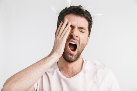 Photo for Image of unshaved man 30s with bristle in casual t-shirt yawning while standing under falling feathers isolated over white background - Royalty Free Image