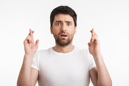 Foto für Image of shocked man 30s with bristle in casual t-shirt keeping fingers crossed and making a wish isolated over white background - Lizenzfreies Bild
