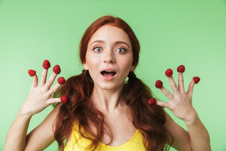 Photo pour Image of a beautiful emotional young redhead girl posing isolated over green wall background with raspberry. - image libre de droit