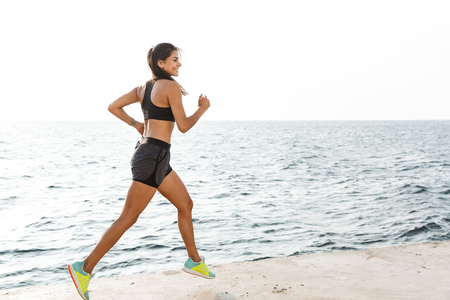 Photo pour Confident fitness woman wearing sportswear running at the beach - image libre de droit