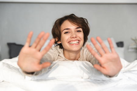 Photo for Cheerful brunette woman having fun and looking at the camera while lying on bed at home - Royalty Free Image