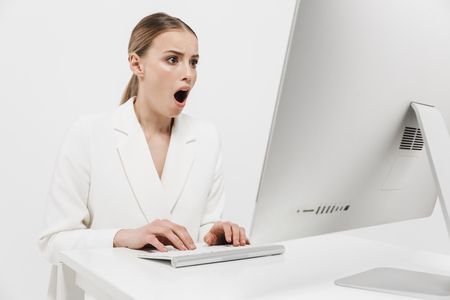 Photo pour Image of a shocked beautiful amazing woman sitting isolated over white wall background using pc computer. - image libre de droit