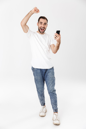 Photo pour Full length of a handsome cheerful man wearing blank t-shirt standing isolated over white background, using mobile phone, celebrating - image libre de droit