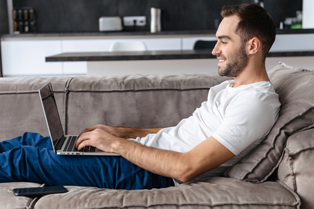 Photo of young guy 30s in casual t-shirt holding and using silver laptop while lying on sofa in bright apartment