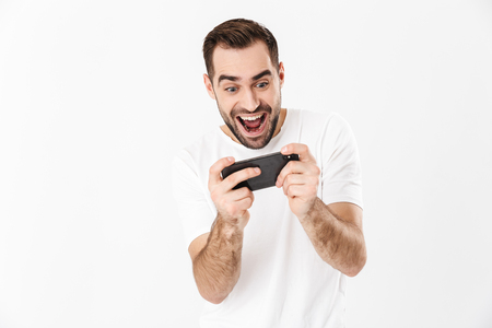 Photo pour Handsome cheerful man wearing blank t-shirt standing isolated over white background, playing games on mobile phone - image libre de droit