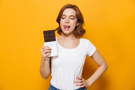 Foto de Portrait of a happy lovely girl standing isolated over yellow background, holding chocolate bar - Imagen libre de derechos