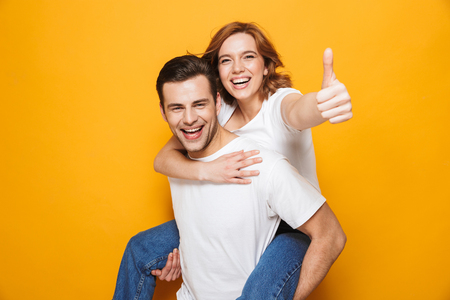 Photo pour Portrait of a cheerful young couple standing isolated over yellow background, piggyback ride, thumbs up - image libre de droit