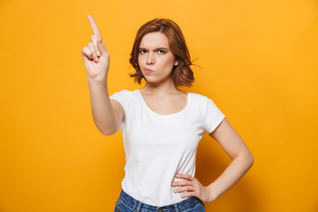 Portrait of a dissatisfied girl standing isolated over yellow background, gesturing