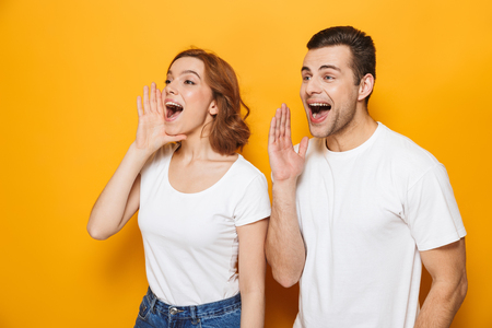 Foto de Portrait of a cheerful young couple standing isolated over yellow background, screaming loud - Imagen libre de derechos