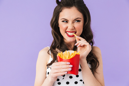 Photo for Photo of caucasian pin-up woman 20s in vintage polka dot dress having dinner and eating french fries isolated over violet background - Royalty Free Image
