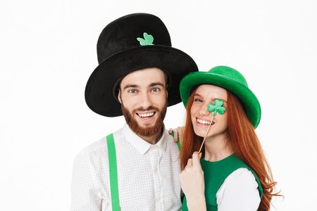 Photo pour Happy young couple wearing costumes, celebrating St.Patrick 's Day isolated over white background, having fun together - image libre de droit