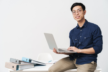 Photo for Photo of smiling asian man 20s wearing eyeglasses sitting at table and working on laptop in office isolated over white background - Royalty Free Image