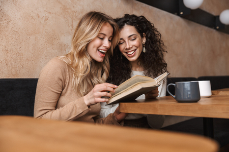 Photo pour Image of excited happy pretty girls friends sitting in cafe drinking coffee reading book. - image libre de droit