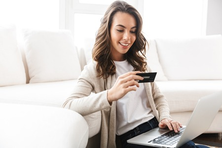 Photo for Beautiful young woman working on laptop computer while sitting at the living room, showing credit card - Royalty Free Image