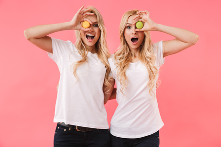 Photo for Funny blonde twins wearing in t-shirts having fun with cakes and looking at the camera over pink background - Royalty Free Image