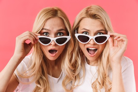 Foto de Shocked blonde twins take off sunglasses and looking at the camera over pink - Imagen libre de derechos
