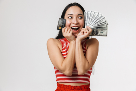 Foto de Photo of a beautiful young pretty asian excited woman posing isolated over white wall background holding credit card and money. - Imagen libre de derechos