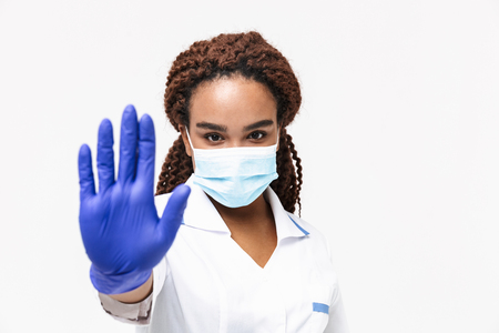 Photo pour Image of young african american nurse or doctor woman wearing medical face mask and disposable gloves showing stop gesture isolated against white background - image libre de droit