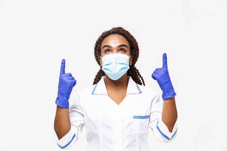 Photo pour Image of happy african american nurse or doctor woman wearing medical face mask and disposable gloves pointing fingers at copyspace isolated against white background - image libre de droit