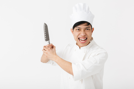 Photo pour Image of asian joyful chief man in white cook uniform smiling at camera while holding big knife isolated over white background - image libre de droit