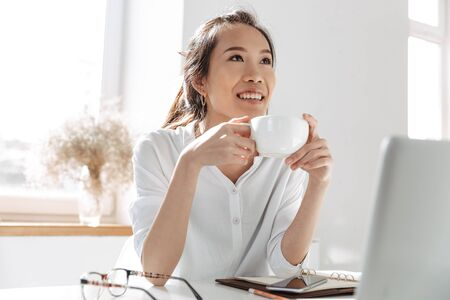 Foto de Pensive smiling asian business woman drinking coffee and looking away while sitting by the table in office - Imagen libre de derechos