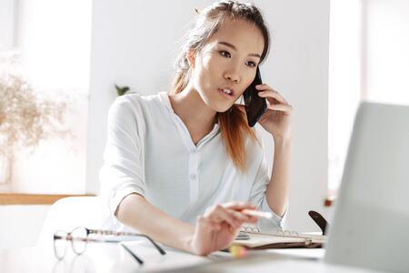Photo for Concentrated asian business woman talking by smartphone and using laptop computer while sitting by the table in office - Royalty Free Image