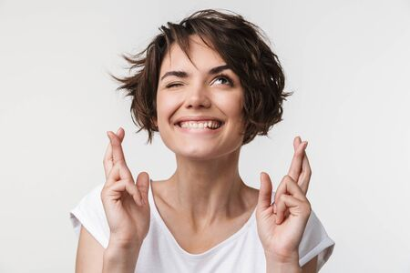 Photo pour Portrait of brunette woman with short hair in basic t-shirt keeping fingers crossed and wishing good fortune isolated over white background - image libre de droit
