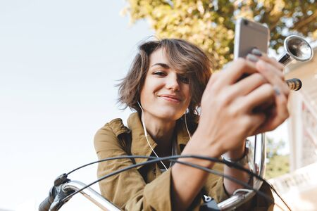 Photo for Picture of a cute young happy cheerful pretty woman walking outdoors in park in beautiful spring day using mobile phone. - Royalty Free Image