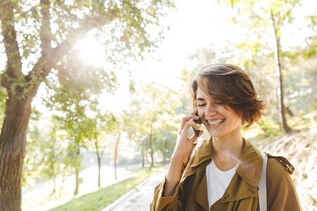 Photo for Image of a cute young amazing woman walking outdoors in park in beautiful spring day talking by mobile phone. - Royalty Free Image