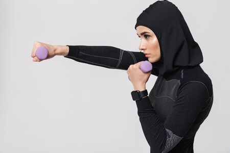 Photo for Image of young woman fitness muslim fighter boxer posing isolated over white wall background make exercises with dumbbells. - Royalty Free Image
