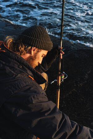 Photo pour Handsome brutal bearded fisherman wearing coat sitting with a fishing rod at the seashore - image libre de droit