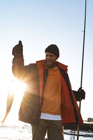 Photo pour Handsome brutal bearded fisherman wearing coat standing with a fishing rod at the seashore, showing caught fish - image libre de droit
